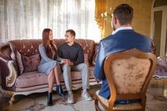 Aux couples de Young de psychologue se reposant sur le divan, vis-à-vis du docteur s'asseyant Photographie stock