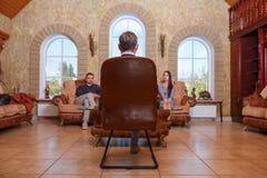 Aux couples de Young de psychologue se reposant sur le sofa, résolvez le problème, docteur s'asseyant dans la chaise écoutant eux images stock