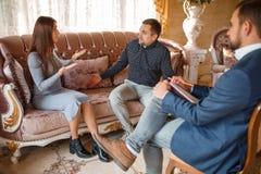 Aux couples de Young de psychologue se reposant sur le sofa, résolvez le problème, docteur s'asseyant dans la chaise écoutant eux photographie stock