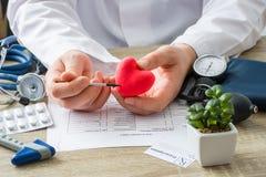 Aux médecins le médecin de rendez-vous montre à la forme patiente du coeur de carte avec le foyer en main avec l'organe Caus pati photographie stock libre de droits