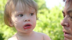 a avó alimenta a sua neta cerejas vermelhas a criança está comendo uma baga madura no jardim nos braços do vídeos de arquivo