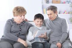 Avó, avô e neto olhando a tabuleta digital ao relaxar no sofá imagens de stock