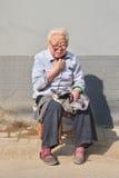 A avó chinesa senta-se fora de apreciar o sol, Pequim, China Fotos de Stock