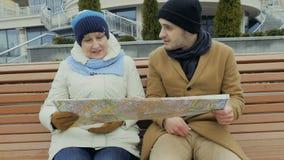 A avó com neto senta-se no banco com o mapa nas mãos vídeos de arquivo