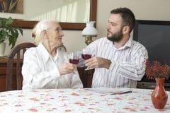 Avó com o neto que senta-se na tabela e no brinde que guardam um vidro do vinho tinto Foto de Stock