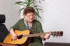 Avó das pessoas de 90 anos para jogar a guitarra Fotografia de Stock