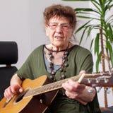 Avó das pessoas de 90 anos para jogar a guitarra Imagens de Stock Royalty Free