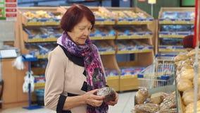 A avó de oitenta anos escolhe e compra o pão na mercearia video estoque