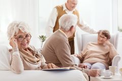 A avó de sorriso lê o livro fotografia de stock royalty free