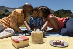 Avó e avô que beijam seu neto ao comemorar seu aniversário no quintal imagens de stock