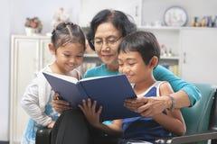 Avó e livro de leitura dos netos junto fotos de stock