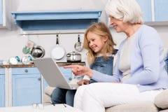 Avó e menina que usa o portátil imagem de stock