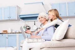 Avó e menina que usa o portátil imagens de stock royalty free