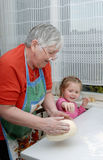 A avó e a neta amassam a massa de pão Imagem de Stock Royalty Free