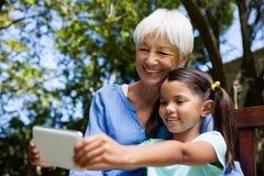 Avó e neta de sorriso que tomam o selfie ao sentar-se no banco Fotografia de Stock