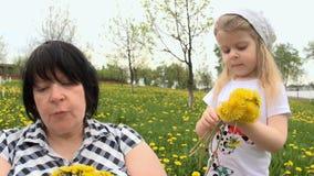 A avó e a neta estão jogando no esclarecimento com dentes-de-leão filme