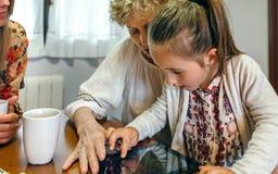 Avó e neta que jogam com tabuleta Imagem de Stock Royalty Free