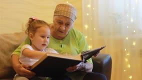 Avó e neta que leem junto o livro do conto de fadas Bisavó que huging seu grande - neta video estoque