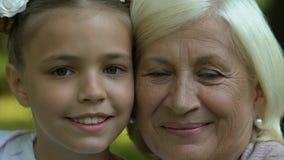 A avó e a neta que olham in camera, geração, enfrentam o close up video estoque