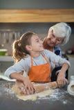 Avó e neta que olham se ao aplainar a massa Imagem de Stock