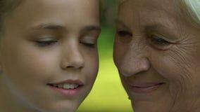 Avó e neta que olham se, levantando para a câmera, fim acima filme
