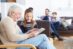 Avó e neta que usa a tabuleta de Digitas junto imagens de stock
