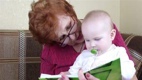 A avó e o bebê leram um livro video estoque