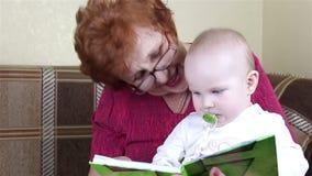A avó e o bebê leram um livro vídeos de arquivo