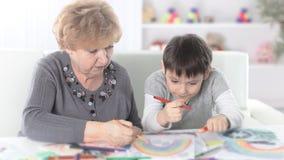 A avó e o neto pintam um arco-íris no berçário fotos de stock