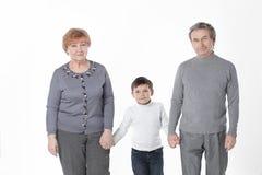 A avó e o vovô vão com seu neto Isolado no fundo branco fotos de stock