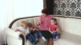 A avó e seus netos sentam-se em casa no sofá filme
