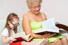 A avó e sua neta estão lendo Imagens de Stock Royalty Free