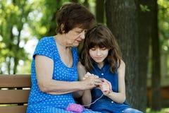 A avó ensina sua neta fazer crochê contra n verde Imagem de Stock Royalty Free