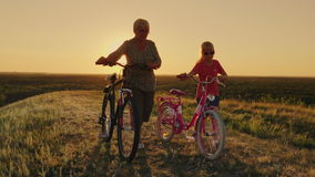 A avó está andando com sua neta Estão andando ao lado, conduzindo bicicletas Um estilo de vida e um active saudáveis video estoque