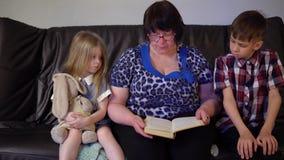 A avó está lendo um livro para netos em casa video estoque