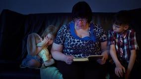 A avó está lendo um livro para netos em casa filme