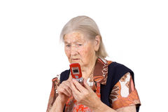 A avó estuda o telefone fotografia de stock