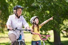 Avó feliz com sua neta em sua bicicleta fotografia de stock