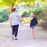 Avó feliz e neta que andam à escola na rua no parque do outono foto de stock