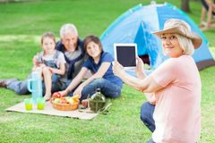 Avó feliz que fotografa a família no acampamento Imagem de Stock