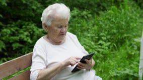 A avó idosa olha o smartphone do Internet filme