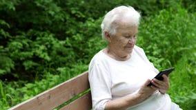 A avó idosa olha o smartphone do Internet video estoque