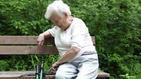 A avó idosa olha o smartphone do Internet vídeos de arquivo