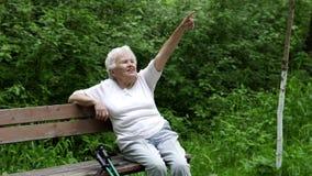 A avó idosa senta o descanso em um banco de parque filme