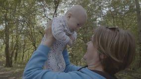 A avó levanta acima e beija o bebê feliz no movimento lento 4k filme