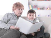 A avó loving lê um livro a seu neto Foto com espaço da cópia imagem de stock royalty free