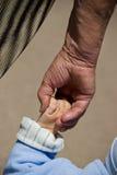 A avó mantem o bebê pelo braço Fotografia de Stock