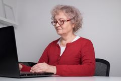 A avó moderna trabalha em um portátil Senhora idosa feliz que fala em um portátil fotografia de stock royalty free