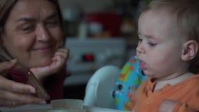 A avó mostra seu neto que é bebê de um ano algo em um telefone celular filme