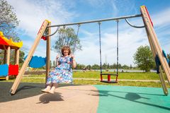 avó mulher adulta que monta um balanço no campo de jogos fotos de stock royalty free
